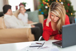 Frustrated mom paying bills during holiday season